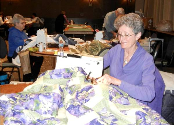VQC member sewing quilt layers together